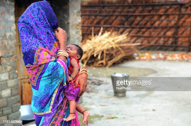 An indian woman stands with her child outside of her home in Harvansh pur village vaishali District some 35 kms from MuzaffarPur Bihar on June 22...