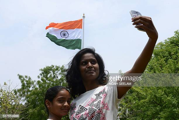An Indian woman takes a selfie as an Indian Tricolour flag flutters on an 83 metre flagpole after being unfurled during a ceremony to mark the Second...