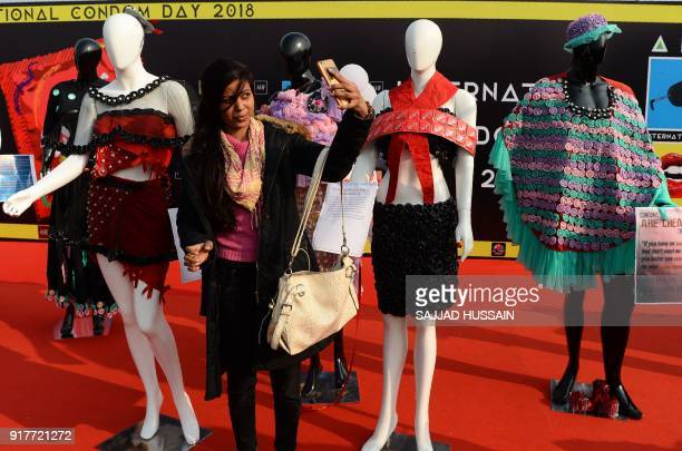 An Indian woman takes a selfie photograph with mannequins wearing a dress decorated with condoms during an event to mark International Condom Day in...