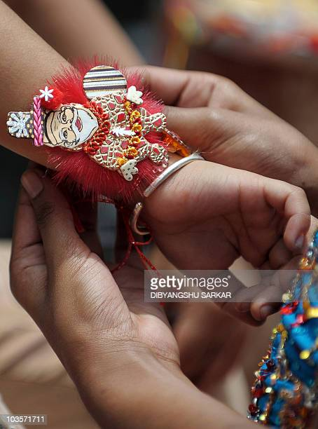 An Indian woman ties a rakhi or sacred thread around her brother's wrist on the occasion of Raksha Bandhan festival in Bangalore on August 24 2010...