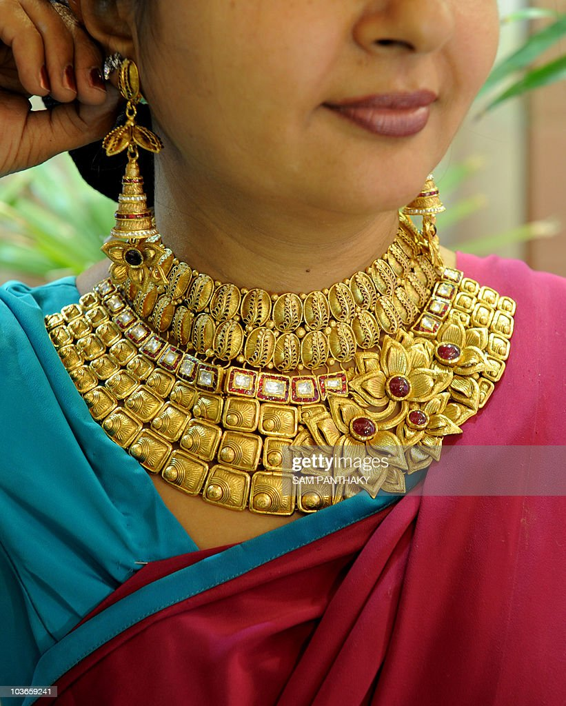 An Indian woman tries on a necklace from Pictures | Getty Images