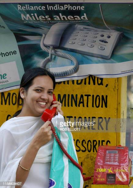An Indian woman uses a public telephone in front of a Reliance IndiaPhone poster in a street of Bombay 02 February 2004 The price of Reliance shares...