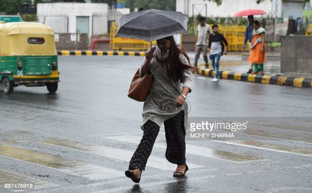 An Indian woman uses an umbrella as it rains in New Delhi on June 19 2017 / AFP PHOTO / Money SHARMA