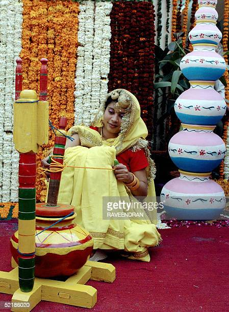 An Indian woman uses traditional implements as she churns milk to make butter at a twoday Railway fair at the Northern Railway Headquarters in New...