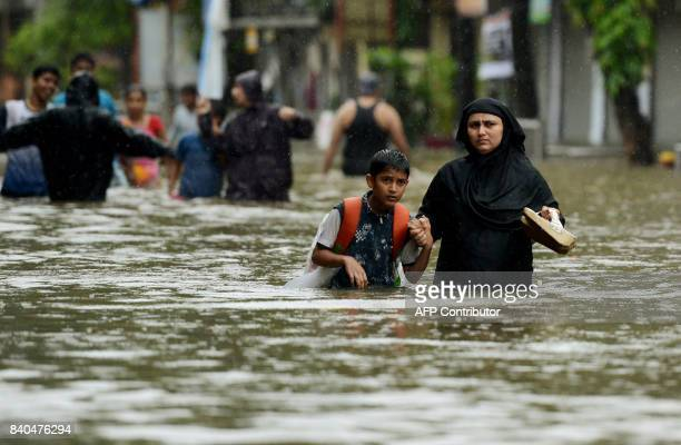 An Indian woman wades with her son through flooded street during heavy rain showers in Mumbai on August 29 2017 Heavy rain brought India's financial...
