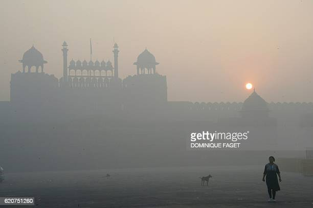 An Indian woman walk near the Red Fort as smog envelop the old quarters of New Delhi on November 3 2016 India's capital with 18 million residents has...