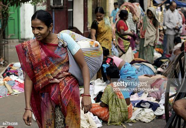 An Indian woman walks away with her purchases as bargain hunters browse through clothing at a second hand clothing market in Kolkata on February 11...