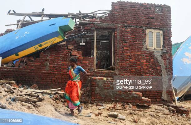 An Indian woman walks next to a damaged building with a fishing boat lodged on its roof along the seafront in Puri in the eastern Indian state of...