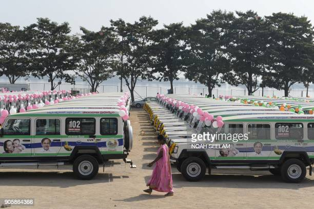 TOPSHOT An Indian woman walks past a fleet of new ambulances during a launch of new vehicles in Hyderabad on January 17 2018 The Telangana government...
