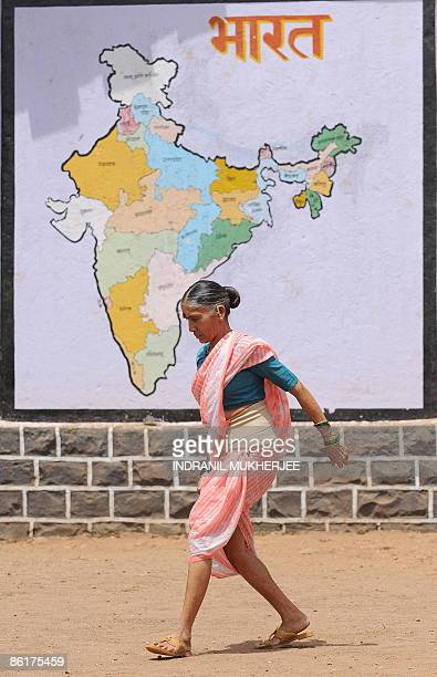 An Indian woman walks past a political map of the country after casting her vote at a polling station in the village of Aamtem in Raigad district of...