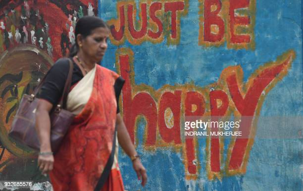 An Indian woman walks past wall graffiti in Mumbai on March 16 2018 The annual World Happiness Report 2018 by United Nations Sustainable Development...