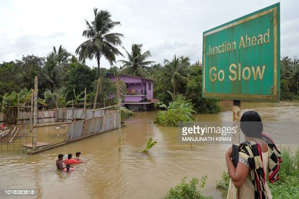 TOPSHOT An Indian woman watches residents walking through flood streets next to their marooned houses on the outskirts of Kozhikode district about...