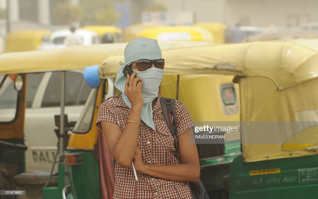 An Indian woman with her face covered against a dust storm speaks on a mobile phone in New Delhi on June 3, 2010. A 40 degrees Celcius and above heatwave has reportedly caused 156 deaths in northern India with today's dust storm forecasted to be interspersed with light rain in some parts of the capital.