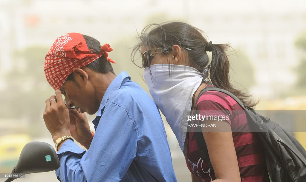 An Indian woman with her face covered against a dust storm travels with a friend on a two wheeler in New Delhi on June 3, 2010. A 40 degrees Celcius and above heatwave has reportedly caused 156 deaths in northern India with today's dust storm forecasted to be interspersed with light rain in some parts of the capital.