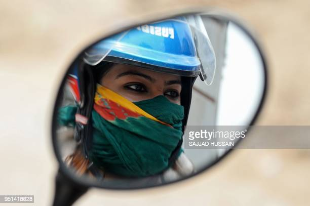 An Indian woman with her face covered sits on a bike during a hot summer day in the old quarters of New Delhi on April 26 2018