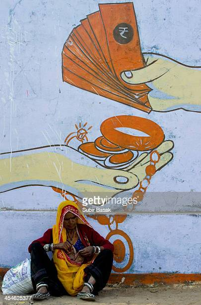 An Indian woman with traditional dresses and ornaments sit in front of a graffiti on a wall in Pushkar during world famous Pushkar Camel festival on...