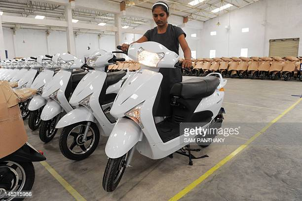 An Indian woman worker test an electric bike at the OREVA E Bike manufacturing facility near Samakhiali of Kutch district some 240 kms from Ahmedabad...