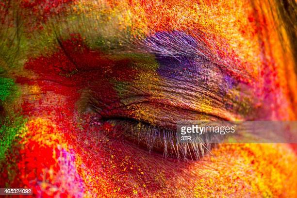 An Indian woman's face is smeared with colored powder during celebrations of the Holi festival in the Sivasagar district of northeastern Assam state...