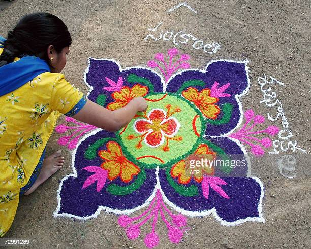 An Indian women applies coloured powder to her Rangoli during a Rangoli competition at shilparamam outskirts of Hyderabad on 13 January 2007 on the...