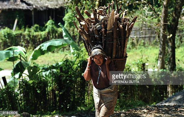 An Indian women carries firewood in Itanagar capital of Arunachal Pradesh northeast India on October 12 2009 With the final countdown for the October...