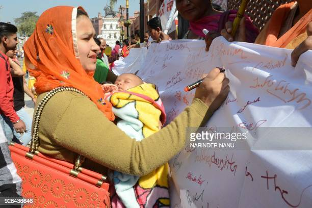 An Indian women carry her girl child as she place her signatures during an awareness campaign 'save the girl child' on the eve of International...