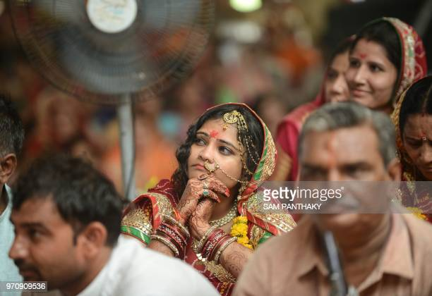 An Indian women from Rajasthan's Nagar community looks on during 'Gangathali' ceremony in the outskirts of Ahmedabad on June 10 2018 Holy water from...