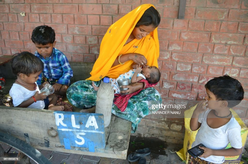 An Indian women gives water to her one month baby girl along with her three sons on a hot summer day at the roadside in Amritsar on May 23 2018