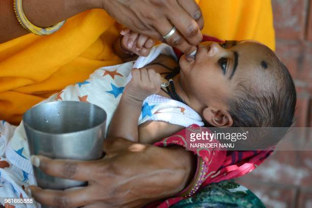 An Indian women gives water to her one month baby girl on a hot summer day at the roadside in Amritsar on May 23 2018