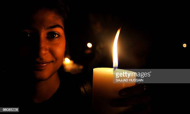 An Indian women lights candle during an Earth Hour campaign in Mumbai on March 27 2010 Dozens of Indians lit candles to observe Earth Hour and called...
