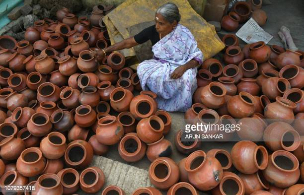 An Indian women sorts dried earthenware pots ahead of the Hindu Pongal festival or Makar Sankranti in a village on the outskirts of Chennai on...