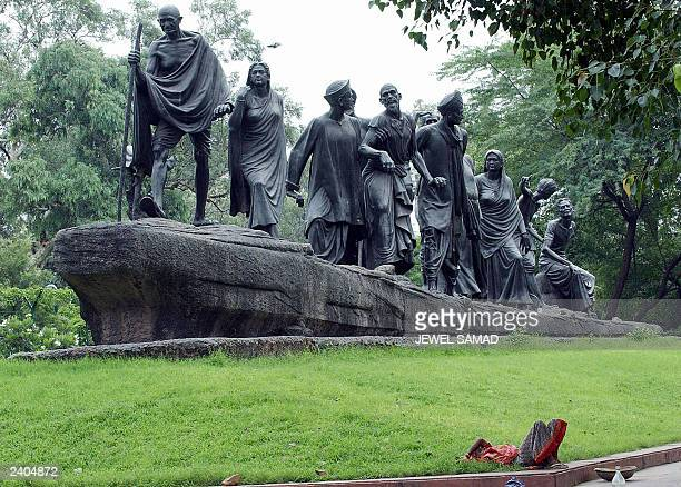 An Indian women takes a break from cleaning a statue which commemerates the Salt March of 1930 and features Indian leader Mahatma Gandhi leading a...