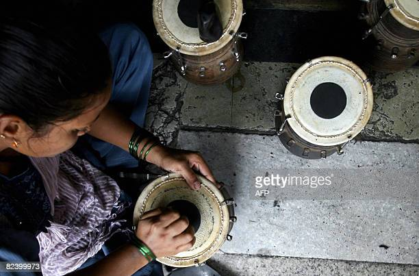 An Indian worker applies the finishing touches to a tabla a traditional Indian percussion instrument to be played during the upcoming Ganesha...