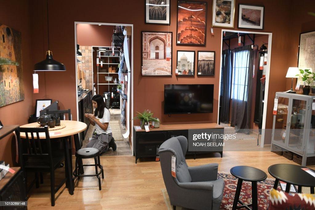 An Indian worker arranges decorations insinde a living room ...