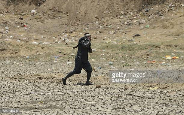 An Indian worker carries a rescued catfish next to a dried up lake on the outskirts of Ahmedabad on May 10 2016 The rescued fish numbering over 100...