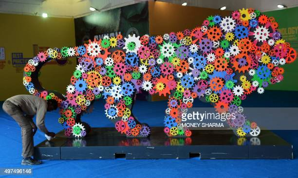 An Indian worker cleans an installation of the 'Make In India' logo at the 35th India International Trade fair in New Delhi on November 17 2015 More...