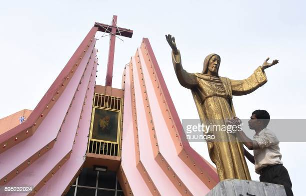 An Indian worker cleans the statue of Jesus Christ at St Joseph's Church in Guwahati on December 19 2017 Christmas is an annual festival...