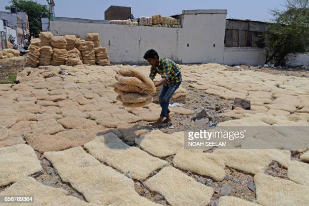 An Indian worker collects pads made of shredded wood fibre at an air cooler factory in Hyderabad on March 23 2017 Air coolers with their moistened...