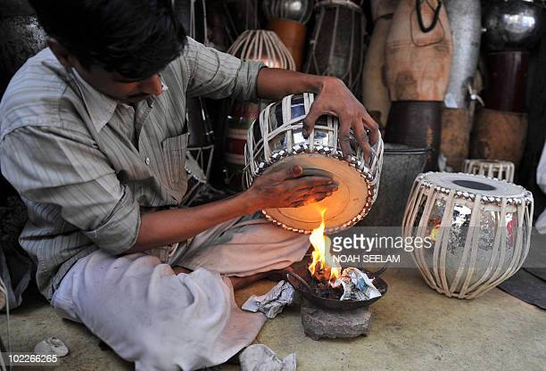 An Indian worker heats the leather of a tabla a traditional Indian musical instrument at a workshop in Hyderabad on June 21 2010 World Music Day is...