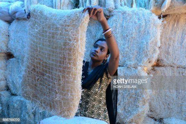 TOPSHOT An Indian worker inspects a pad made of shredded wood fibre at an air cooler factory in Hyderabad on March 23 2017 Air coolers with their...