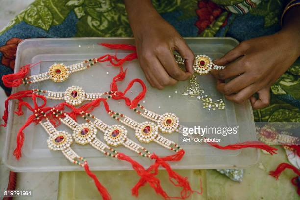 An Indian worker makes a speciallydesigned bracelets known as rakhis ahead of the Raksha Bandhan festival at a workshop in Hyderabad on July 20 2017...