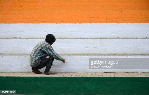 TOPSHOT An Indian worker paints stairs at a stadium iin the colours of the Indian national flag ahead of events to mark Republic Day in Allahabad on...