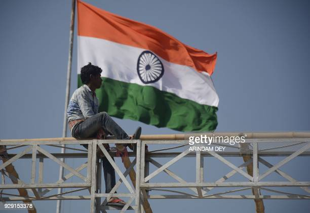 An Indian worker prepares a stage ahead of the swearingin ceremony for council of ministers of Tripura legislative assembly at Assam Rifles ground in...