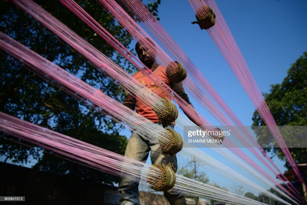 An Indian worker prepares coloured kite strings at the roadside ahead of the forthcoming Lohri Festival in Jalandhar on January 9 2018 The Lohri...