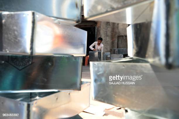 An Indian worker prepares parts for water coolers at a market in the old quarters of New Delhi on May 29 as demand for cooling equipment surges at...