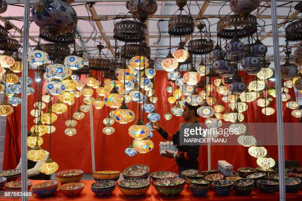 An Indian worker sets light bulbs on turkish lanterns during The Punjab International Trade Expo PHD 2017 Trade Fair in Amritsar on December 7 2017...
