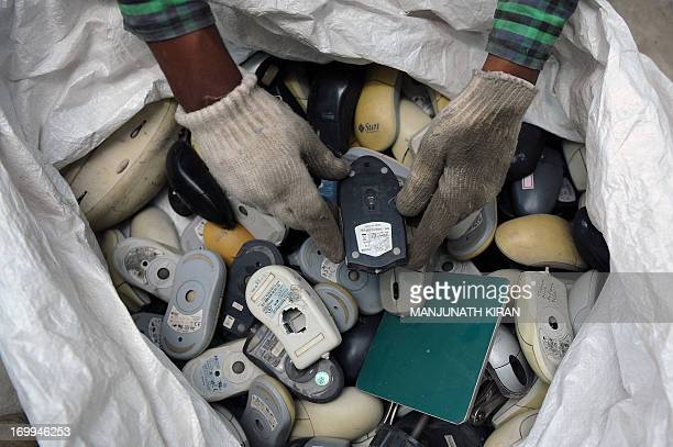 An Indian worker sifts through a bag full of defunct computer mice prior to disassembly at Ash Recyclers a government approved ewaste management firm...