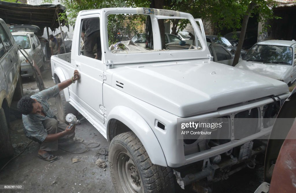 An Indian worker spraypaints a jeep at car repair workshop in Amritsar on July 1 2017 / AFP PHOTO / NARINDER NANU