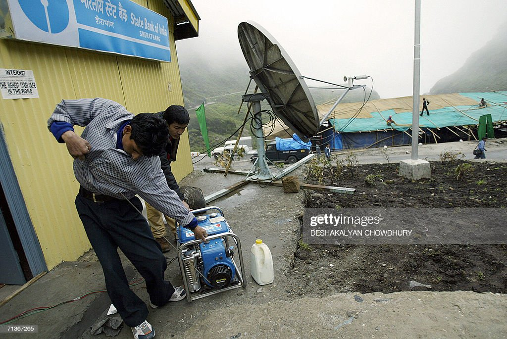 An Indian worker starts a generator to set up an Internet