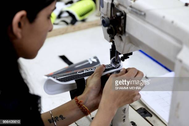 An Indian worker stitches a shinguard ahead of the Russia 2018 FIFA World Cup at a manufacturing unit in Jalandhar on May 9 2018