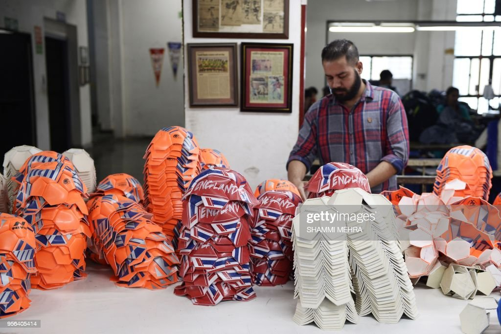 An Indian worker stitches footballs ahead of the Russia 2018 FIFA World Cup at a manufacturing unit in Jalandhar on May 9 2018